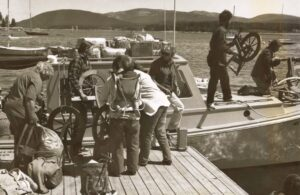 people loading spinning wheels on boat