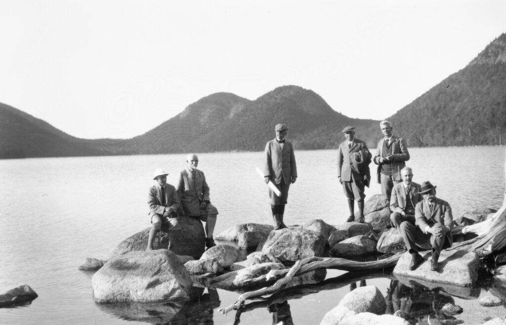 Gentlemen pose on rocks at pond's edge.